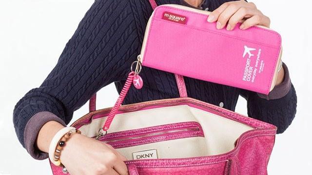 Фото девушка кладет в сумку розовый дорожный органайзер для документов. Товары для отдыха. Интернет-Магазин В Отпуск