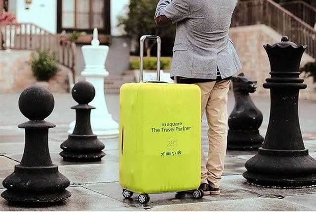 Фото на улице большого чемодана в салатовом эластичном чехле. Товары для отдыха. Интернет-магазин В Отпуск размера L.