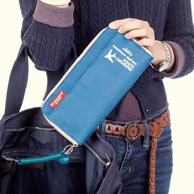Синий дорожный органайзер для документов, билетов, посадочных талонов и денег. Фото в руках у девушки