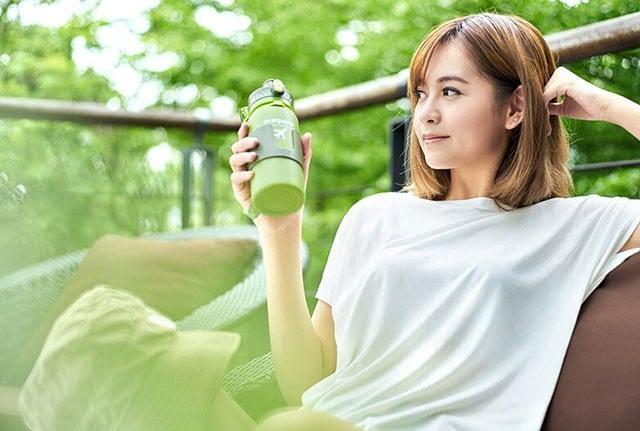 Фото релакс на фоне природы с зеленой силиконовой бутылочкой для воды. Товары для отдыха. Интернет-магазин В Отпуск