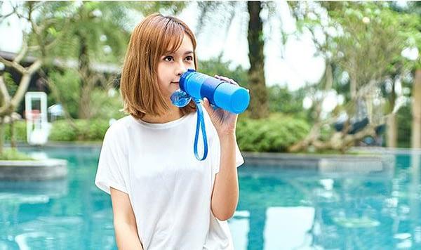 Фото девочка пьет из голубой силиконовой бутылочкой для воды. Товары для отдыха. Интернет-магазин В Отпуск