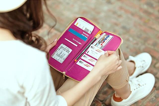 Фото развернутый розовый органайзер для документов в руках у девушки. Товары для отдыха. Интернет-магазин В Отпуск